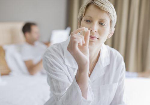 Woman looking at pill