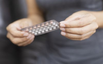 Woman holding birth control pill pack.
