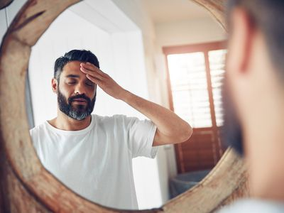 Exhausted man in bathroom mirror