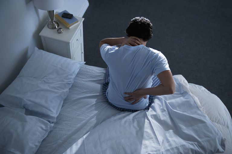 Man with back and neck pain on the bed