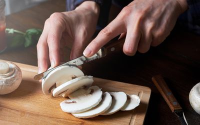 Close up of a white person's hands slicing a white mushroom.