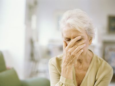 A woman covering her face with her eyes closed