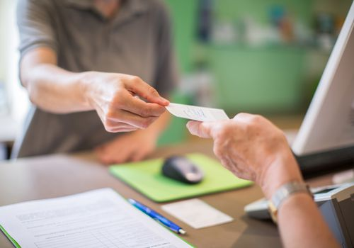 Close-up of a receptionist giving a health card to female patient at clinic. Focus on hands of female with a health card.