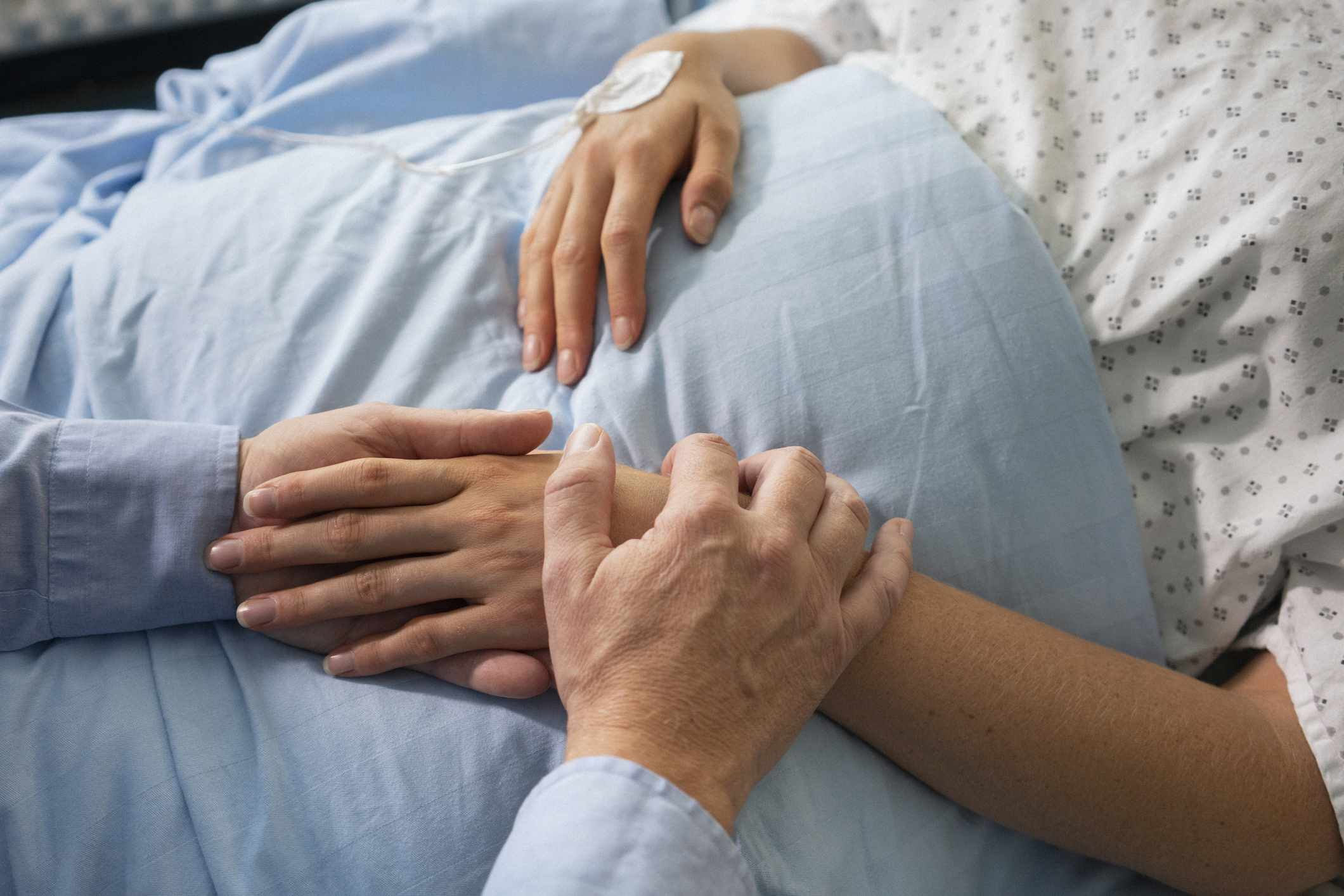Man comforting female patient recovering in hospital bed