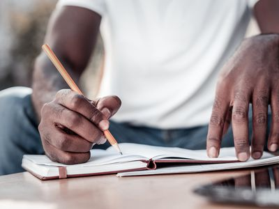 Close up of african american man taking notes - stock photo