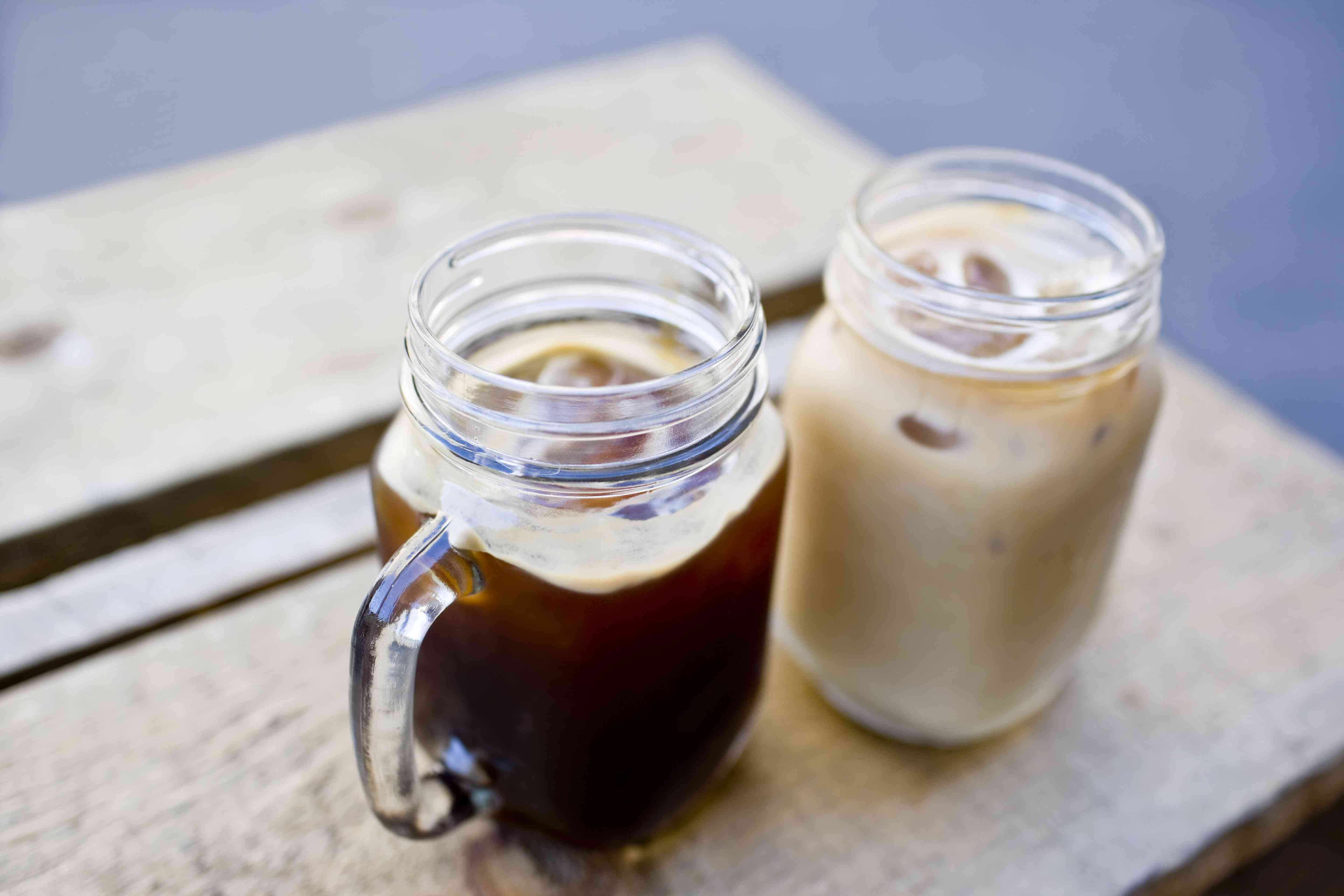 Two iced coffees in glass mugs on an outside table