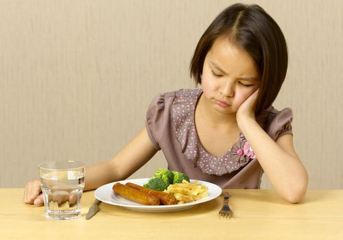 Determined girl refusing to eat a plate of food