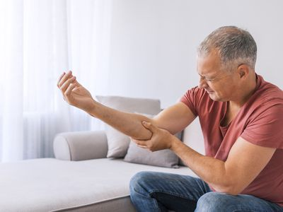 man experiencing sharp pain in elbow