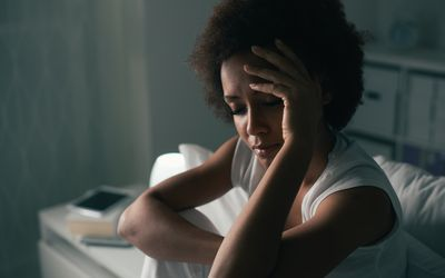 Sad woman suffering from insomnia while sitting on her bed