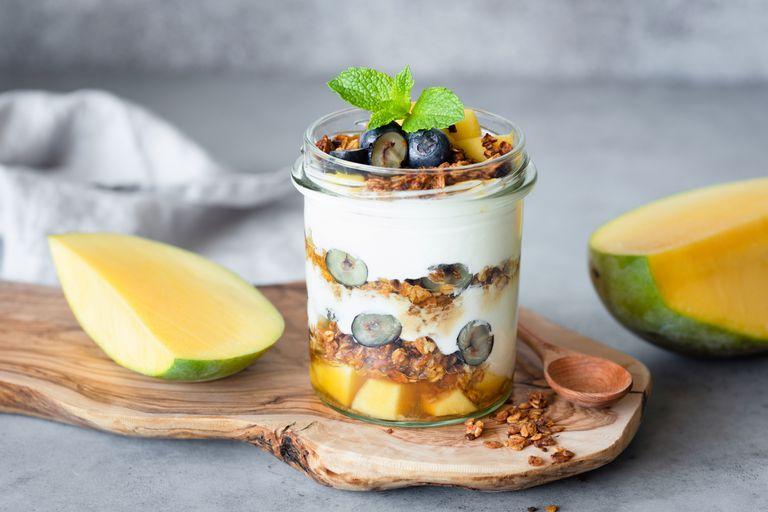 Breakfast yogurt parfait with granola, mango, berries in jar