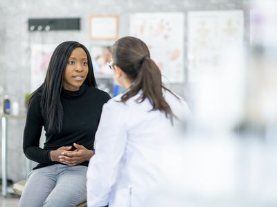 A woman explaining her symptoms to a physician while holding her stomach.