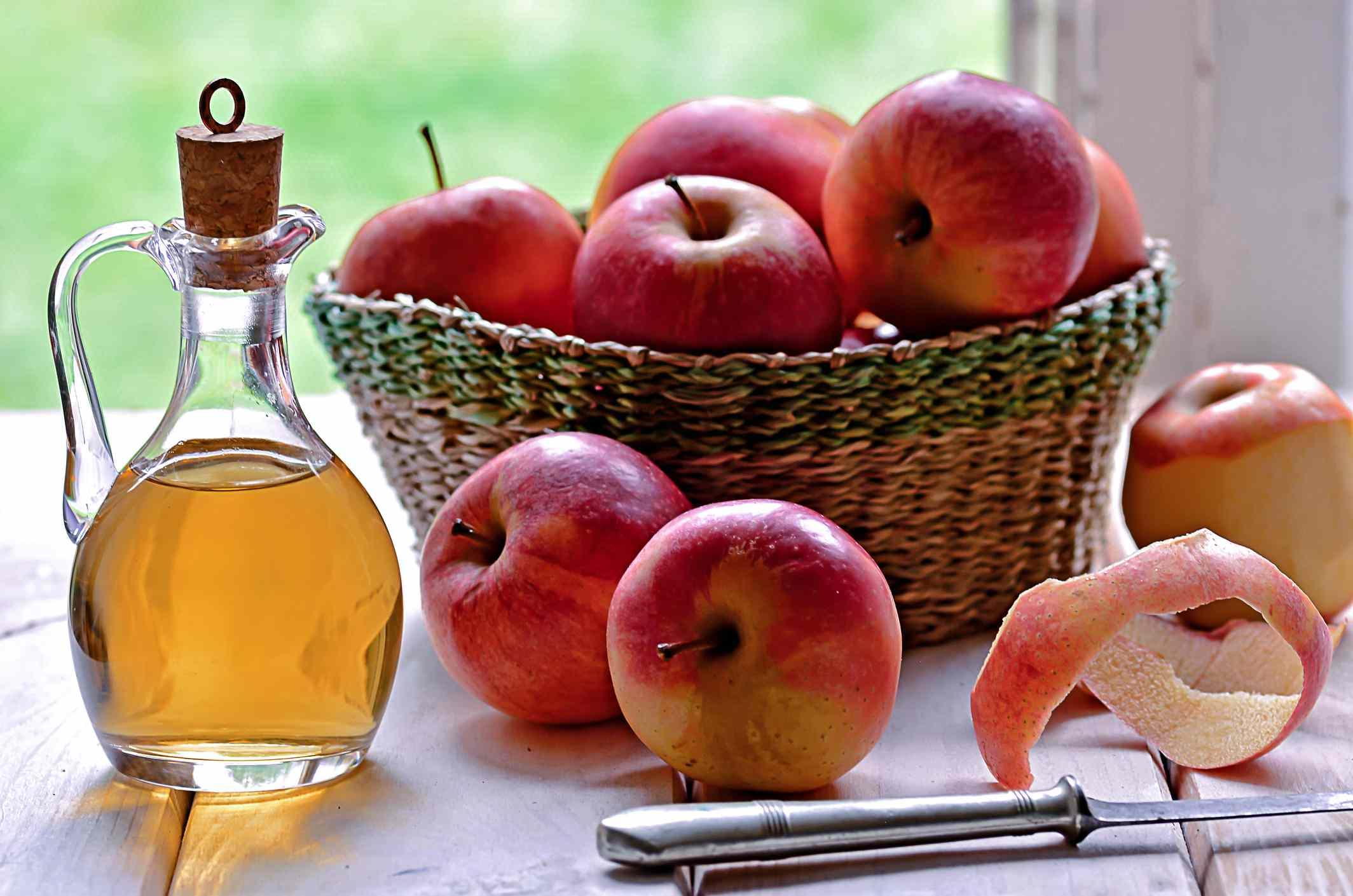 Bottle of apple cider vinegar next to a basket of apples