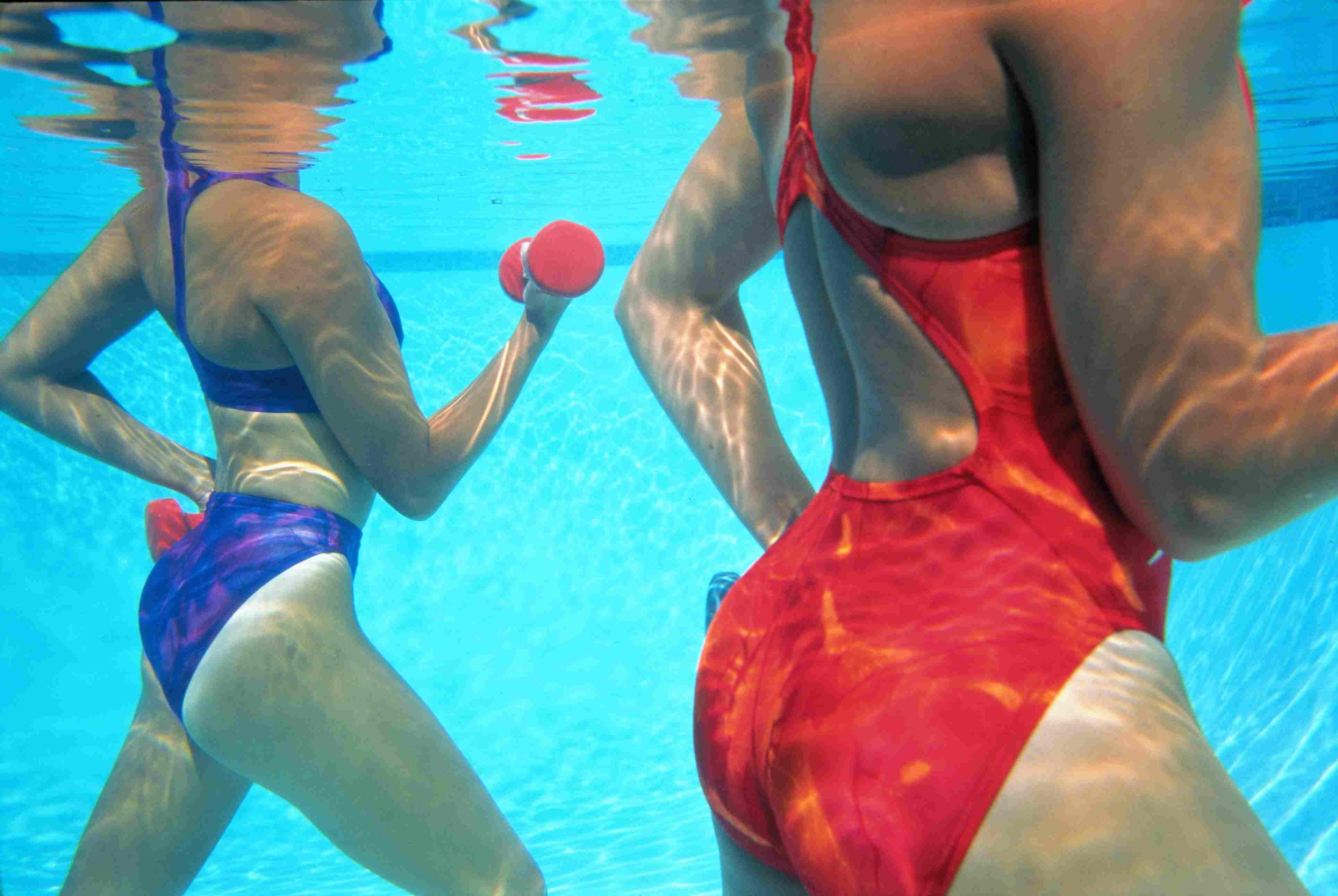 Two women power walk in the water
