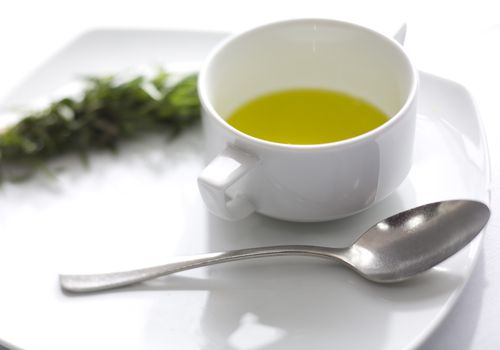 Broth in a white cup next to a spoon