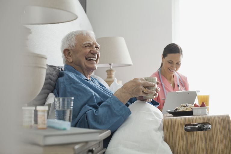 Senior man sitting with home care nurse eating breakfast