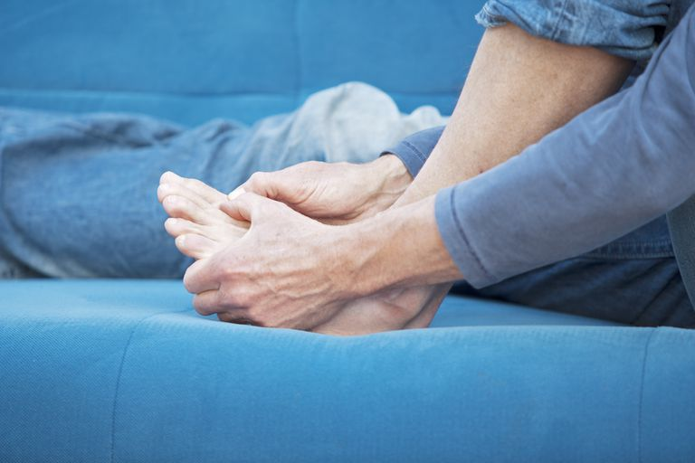 woman holding painful foot, feeling for broken toe