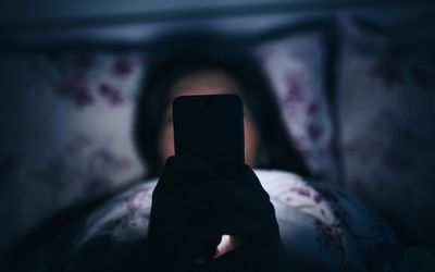 Woman reading and texting on smartphone in bed
