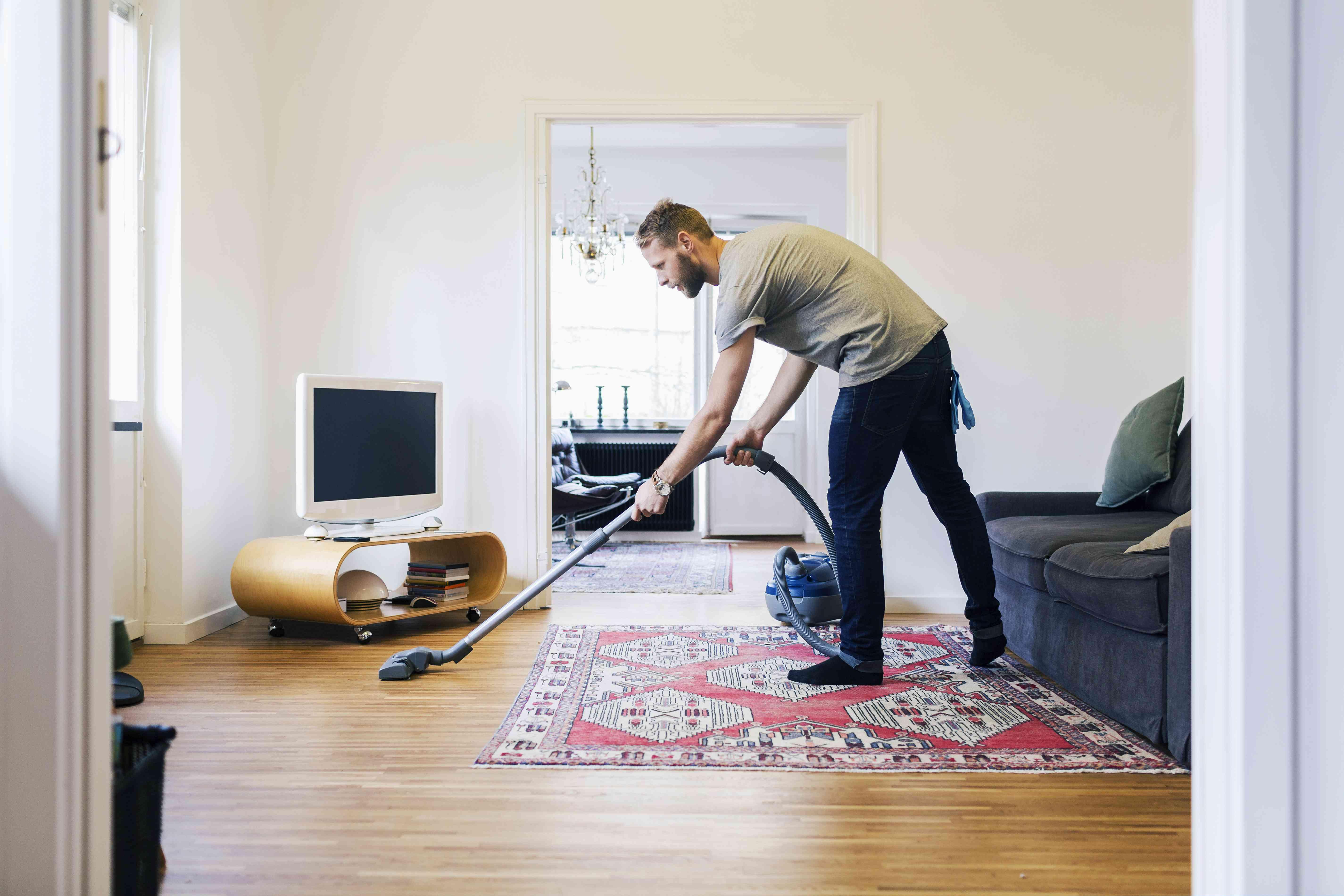 Side view of man vacuuming hardwood floor