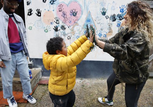 Mother and son touching hands covered in wet paint