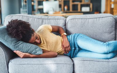 Shot of a young woman experiencing stomach pain while lying on the sofa at home