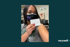 Young woman takes photo with COVID-19 vaccine card.
