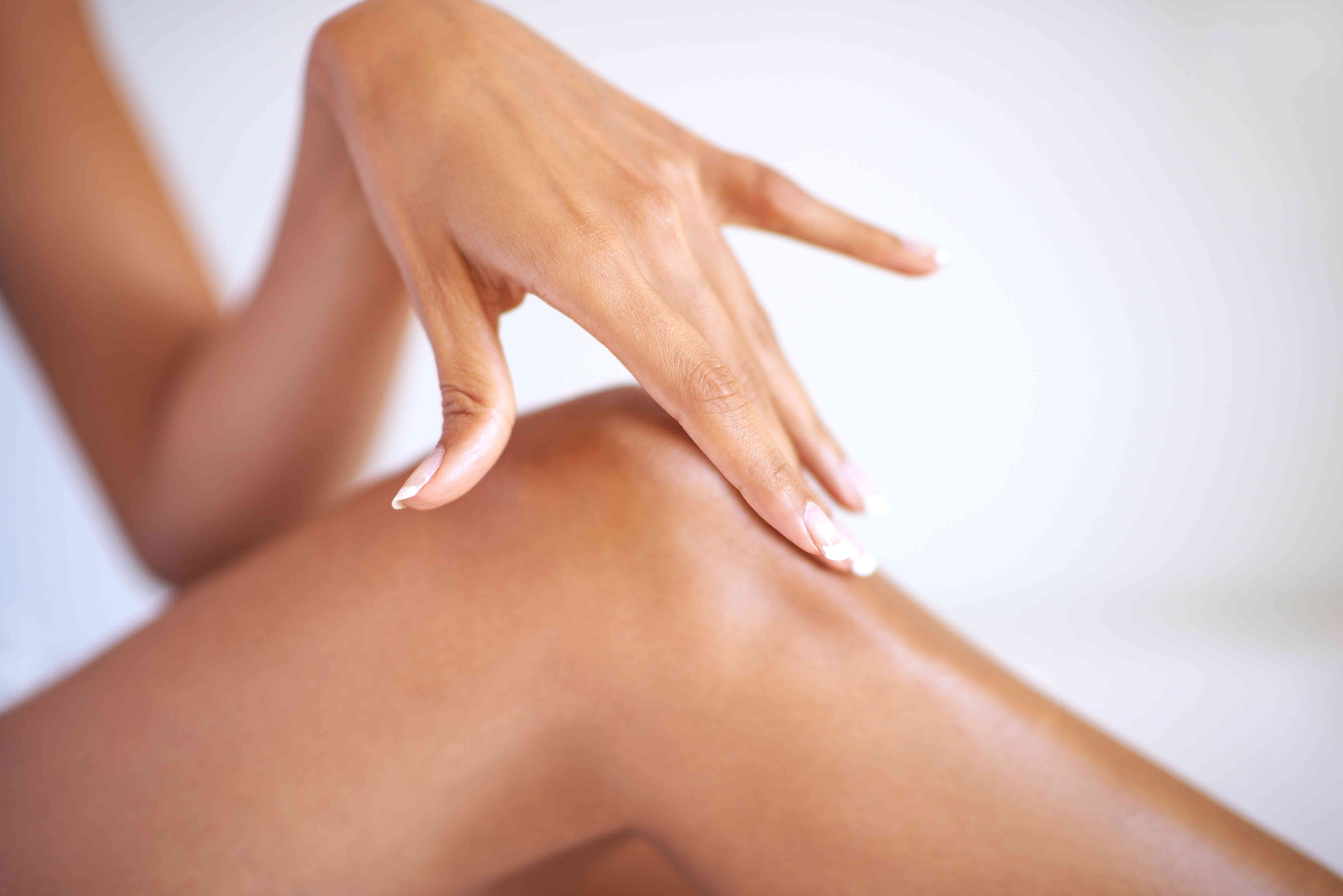 A woman caressing the skin of her knee