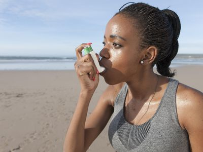 young jogger using asthma inhaler on the beach