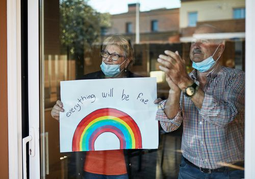 Two older adults wearing masks standing by their glass door.