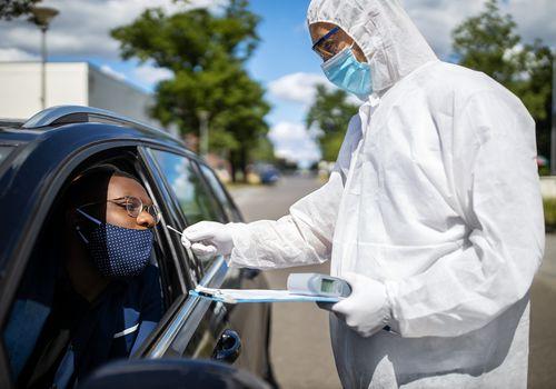 Someone receiving a COVID-19 exam in their car.
