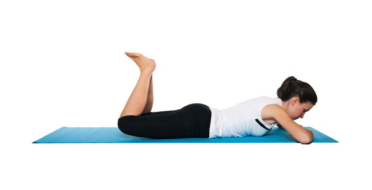 A woman is lying on her stomach and strengthening her hamstring muscles.