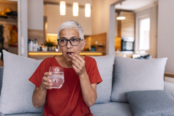 Woman with pill and glass of water
