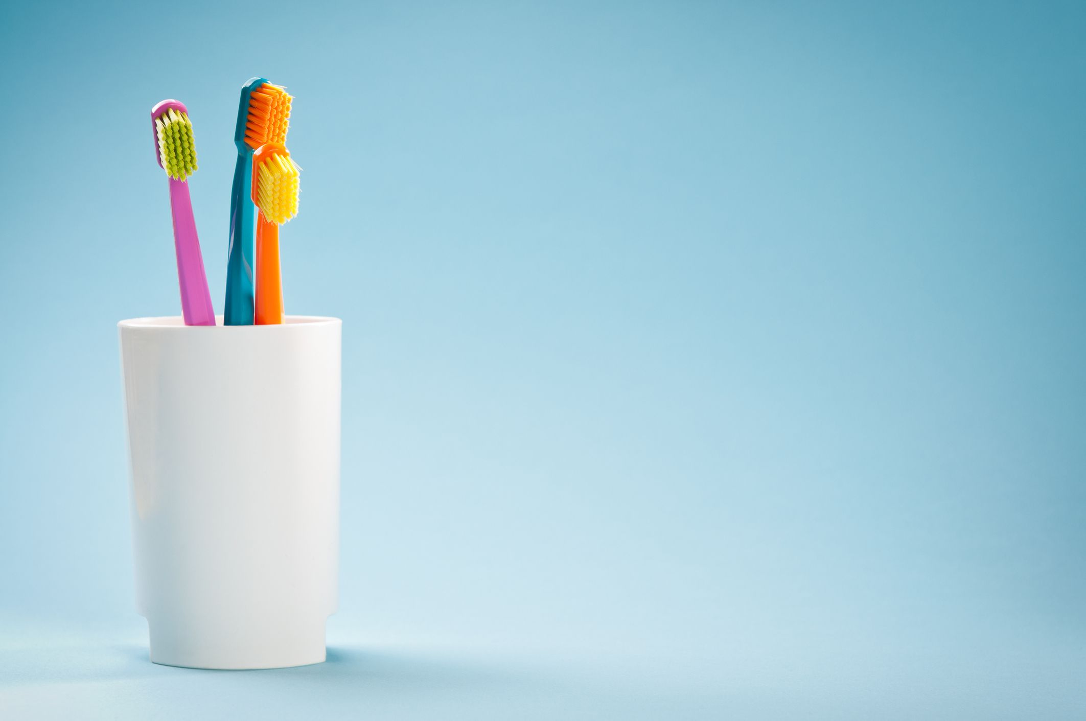 Three toothbrushes in a white cup