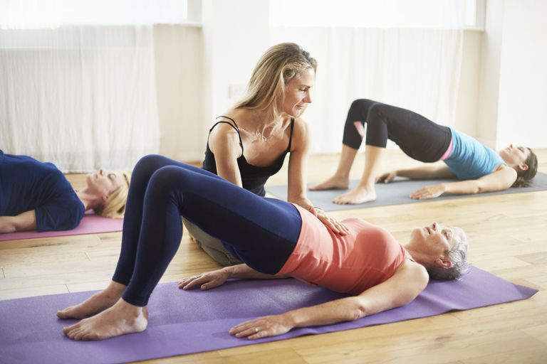 young woman helping older woman with a lower back yoga pose