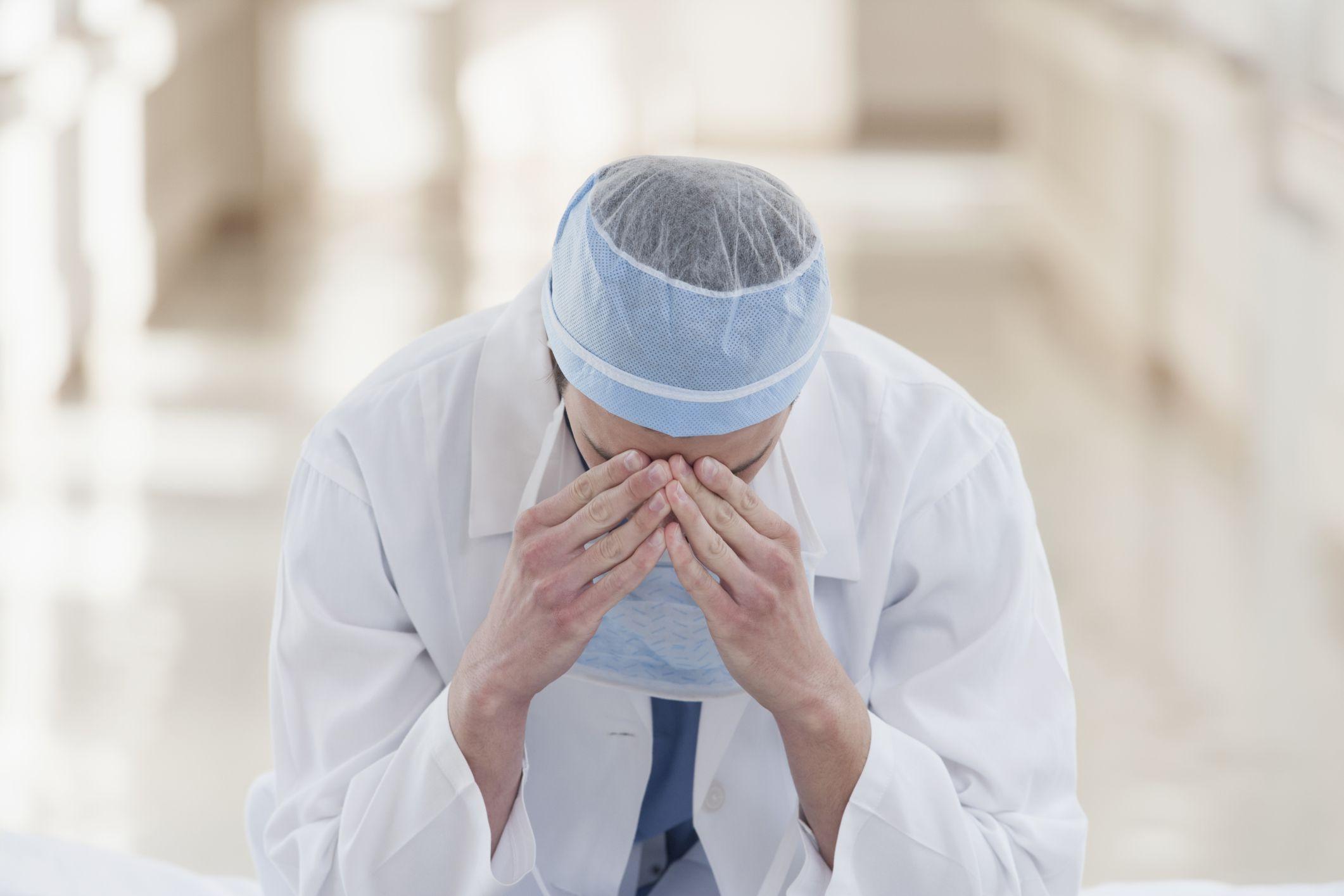 Upset doctor with head in hands