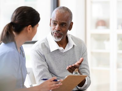 Older man speaks with a healthcare provider.
