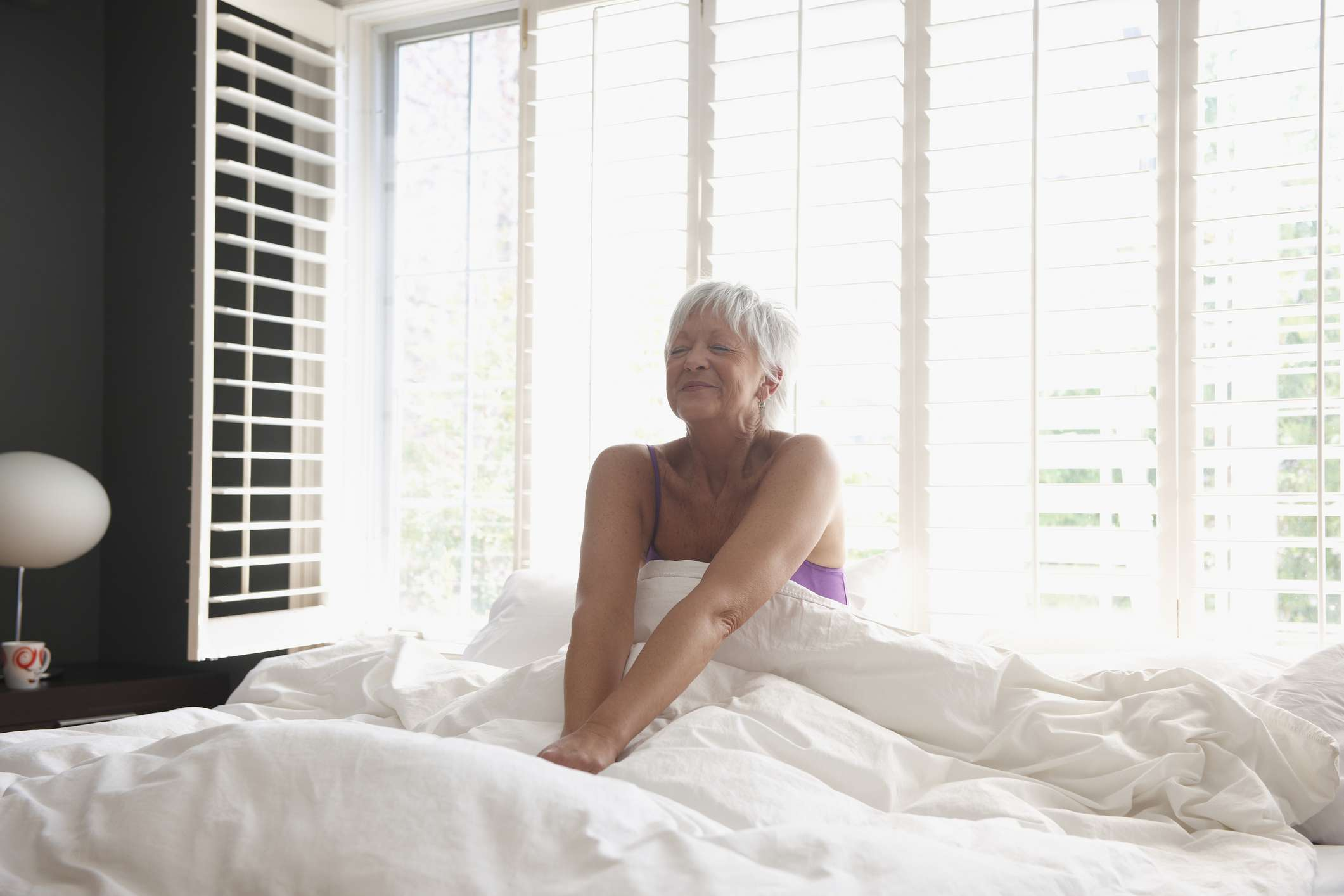 An older woman waking up in bed