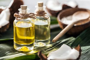 selective focus of bottles with coconut oil near cracked coconuts on green palm leaves
