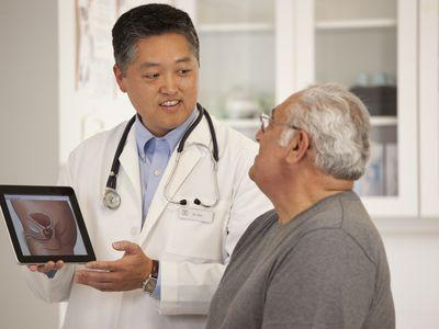 Doctor using digital tablet to talk to senior man.