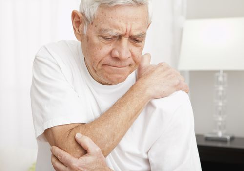 elderly man holding elbow in discomfort