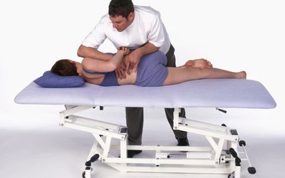 A chiropractor adjusts a patient.