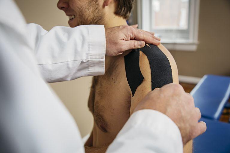 Doctor applying shoulder tape to patient