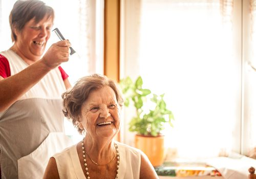 Caregiver combing hair of woman with dementia