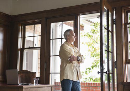 a man gazing outside through an open patio door
