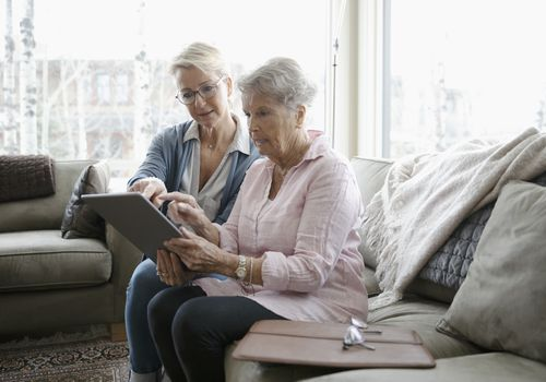 Daughter helping senior mother using digital tablet - stock photo