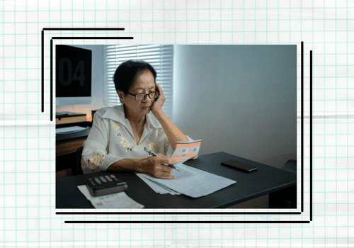 Older woman looking at her bills and receipts for the month.