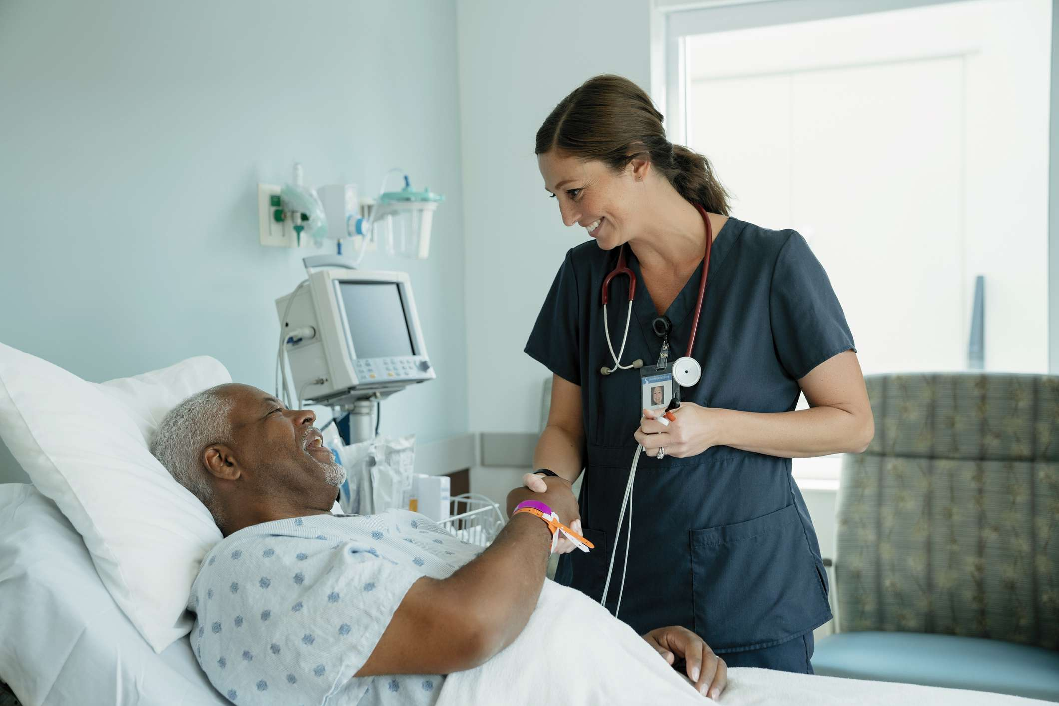 Smiling nurse handshaking with senior patient lying on bed in hospital ward - stock photo