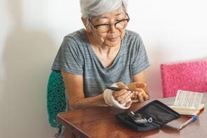 woman checking blood sugar at home
