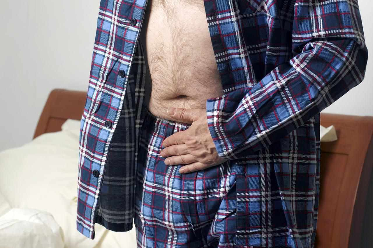 Man with constipation holding his stomach