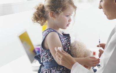 Doctor giving toddler girl a shot