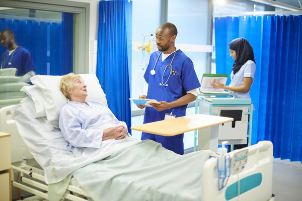 A patient receives instruction from her care team in a hospital setting.